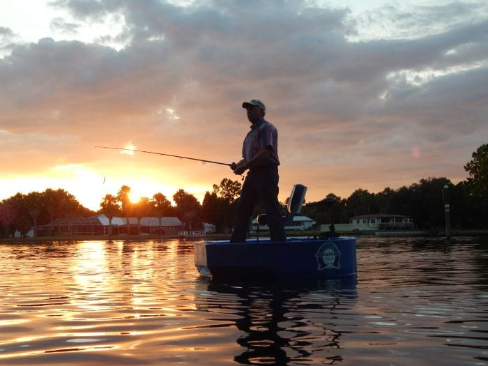 A blue rond boat and a fisherman at sunset on the water in a bay