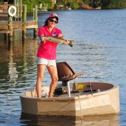A female fisherman with a snook caught by a dock on a tan round boat