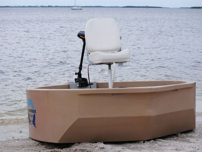 A tan round boat with a front view on the shore
