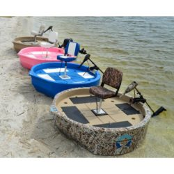 This is 4 round boats sitting on the shore. They are camo, blue, pink, and tan in color, top view