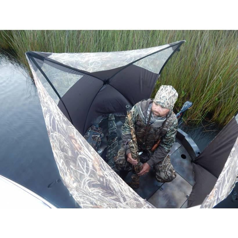 This is a on the water view of the round boat hunting blind by ameristep. Shows hunter with a shotgun inside of this hunting boat.
