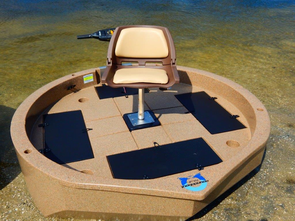 This is a top view of a sandstone colored round boat with white trim sitting on the shore