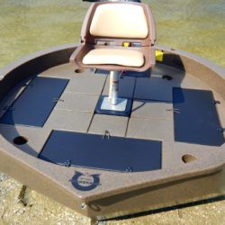 This is a top view of a moss granite colored round boat with white trim sitting on the shore