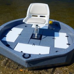 This is a top view of a slate colored round boat with white trim sitting on the shore
