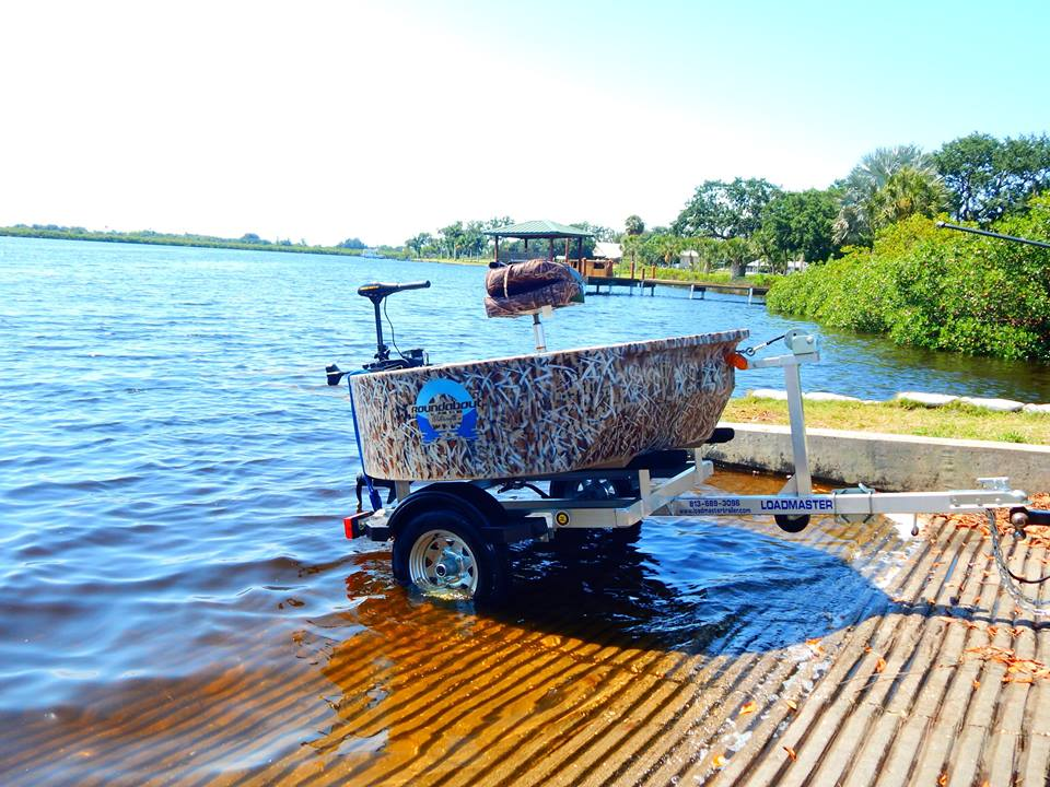 This is the woodsman hunting boat at a boat ramp sitting on a trailer.