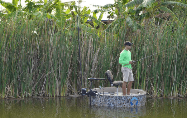 Smaller view of a fisherman fishing on the rond boat near the shore of tall grass