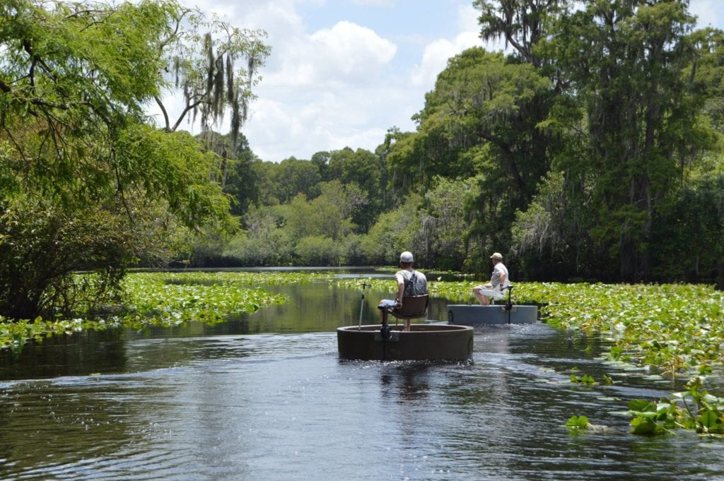 Two fisherman driving their round boats down a river