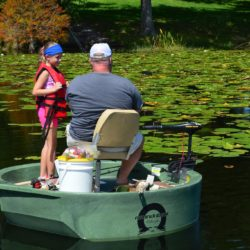 A father and daughter fishing from a green round boat for bass while both on the boat at the same time