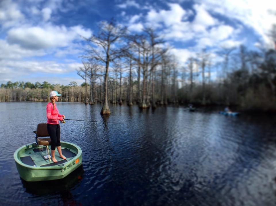 A female fisherman fishing the backwatrs of north florida while standing on the deck of a green round boat