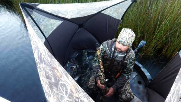 There is a waterfowl hunter sitting in a hunting blind on the deck of this hunting boat.
