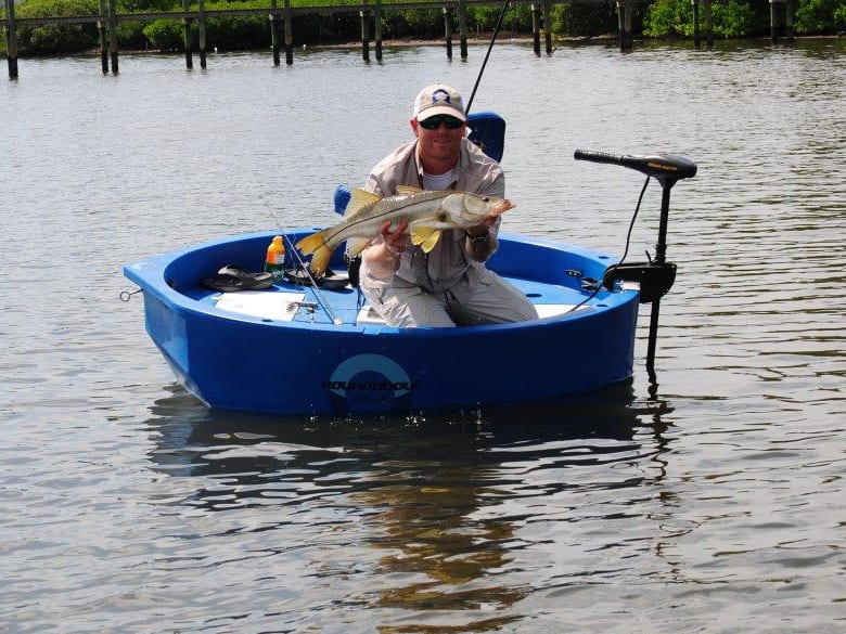 Angler with a freshly caught snook in a round boat
