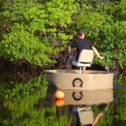 Fisherman driving a round boat near the shoreline with an electric trolling motor.