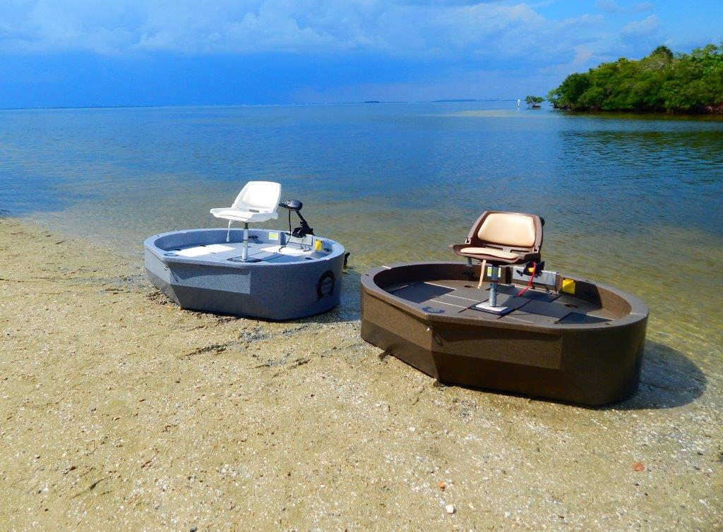 two roundabout watercrafts, the ultraskiff alternative, sitting on the shoreline. One is blue, one is a brown color.