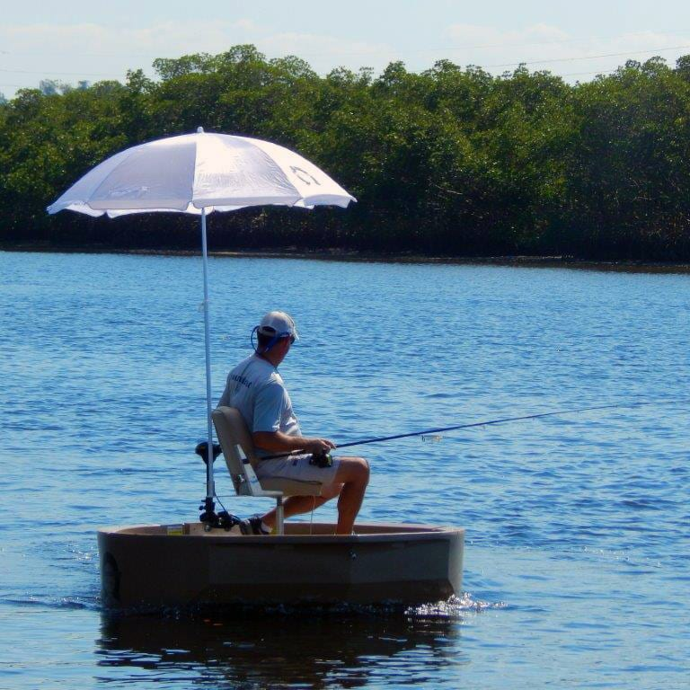 An angler fishing from a round boat with the sunshade attached