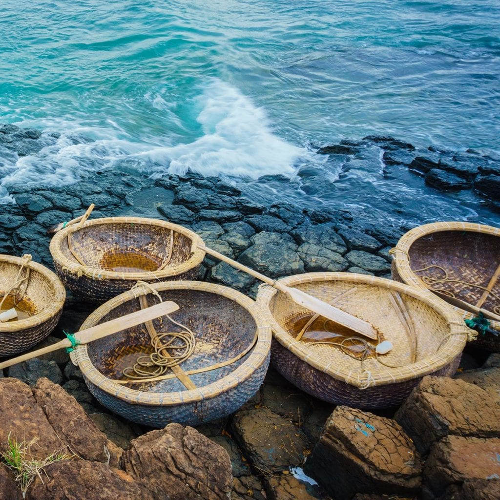 This shows traditional coracle style round boats sitting on a rocky shoreline